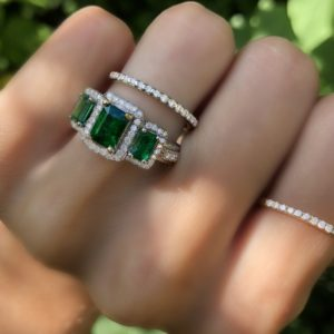 Three Stone Emerald Ring in Diamond Halo  Center Emerald: 1CT - AA  Side Emeralds: 0.60CTW - AAA   Diamond Halo: 0.39CTW - Clarity: Si1 - Color: G  14K White Gold  $7800-